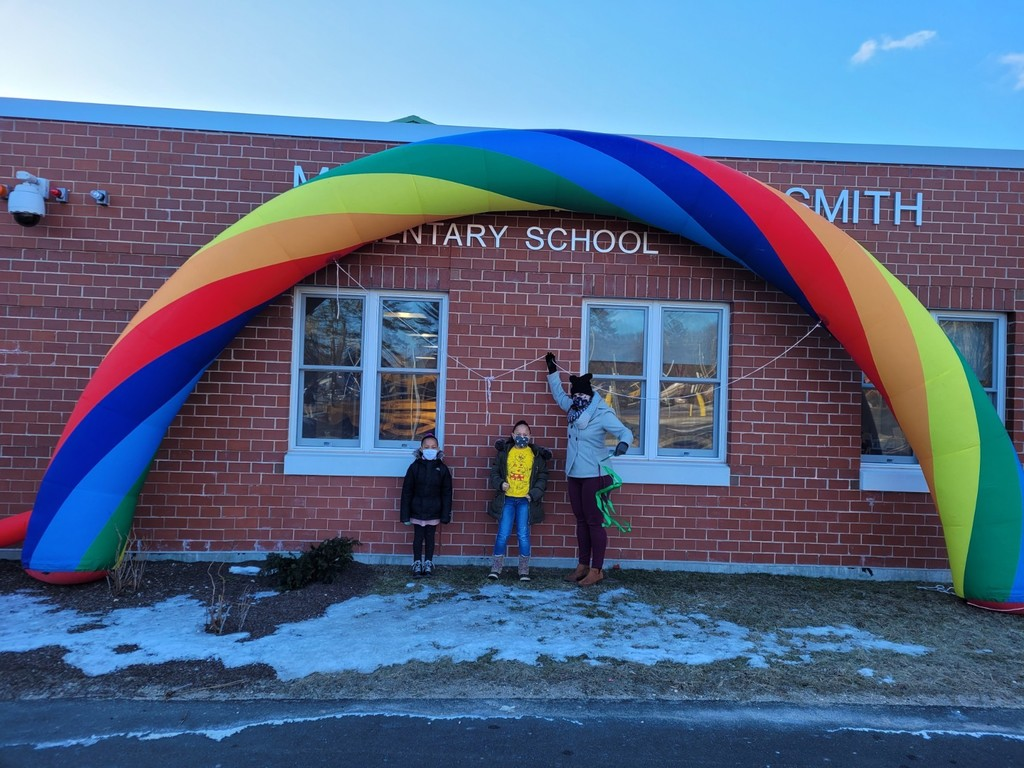 Two student and Ms. Hastings under our inflatable rainbow.